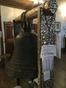 America's oldest Bell in the Oldest Church - with whole bunch of Milagros (representing miracles) pinned into the wood